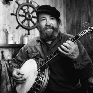 Barney McKenna of the Dubliners plays his banjo at home in Howth ireland 1995. Barney had just come back from sailing his old fishing trawler along the coast nearby.