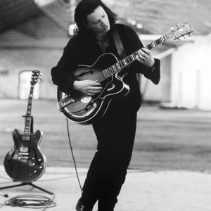 "Bono of U2 practising guitar at the Point depot in Dublin 1989. The band used this location which was a disused train repair shop for the filming of Rattle and Hum"". After this use the building was refurbed into a large music arena."