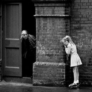 A Child and an old woman in inner city Dublin play on the street in 1976 - The Iveagh buildings in the Liberties quarter.