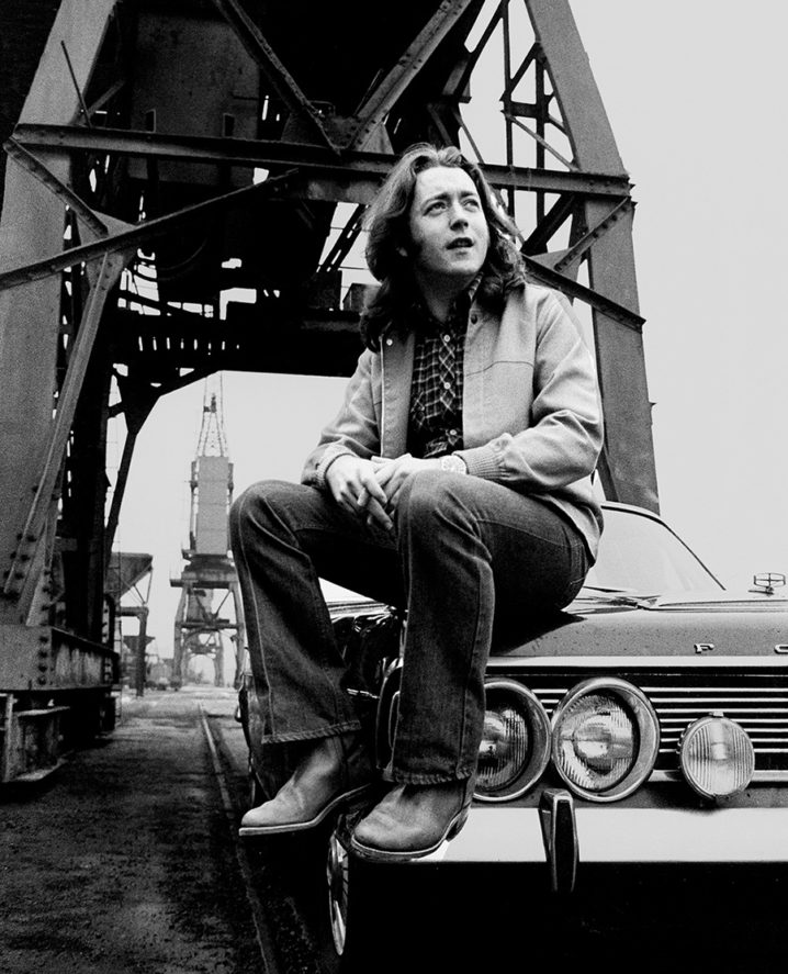 Rory Gallagher sits on his old Ford Granada in the docklands of Cork city in 1981.