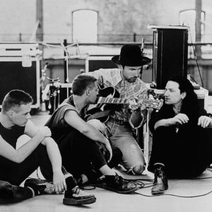 """Edge of U2 showing some new ideas to the band in summer of 1988. The band used this location which was a disused train repair shop for the filming of Rattle and Hum"""". After this use the building was refurbed into a large music arena."""