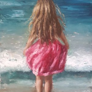Long haired little girl in a pink dress looking into the Atlantic Sea