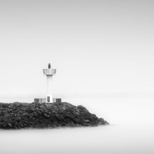 A black and white photograph of the lighthouse beacon in Howth harbour