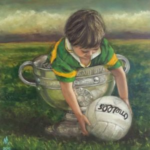 Small boy wearing a Kerry jersey in the Sam Maguire reaching out to capture an O'Neills football.