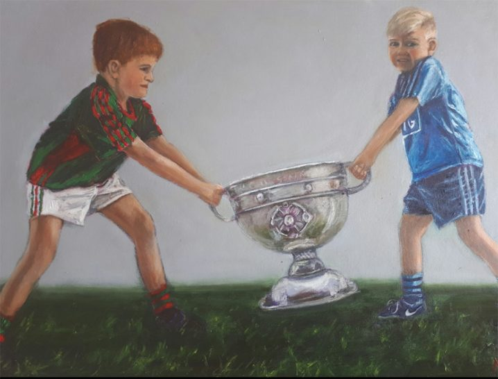 Boy wearing a Mayo jersey pulling the Sam Maguire from a boy wearing a Dublin jersey.
