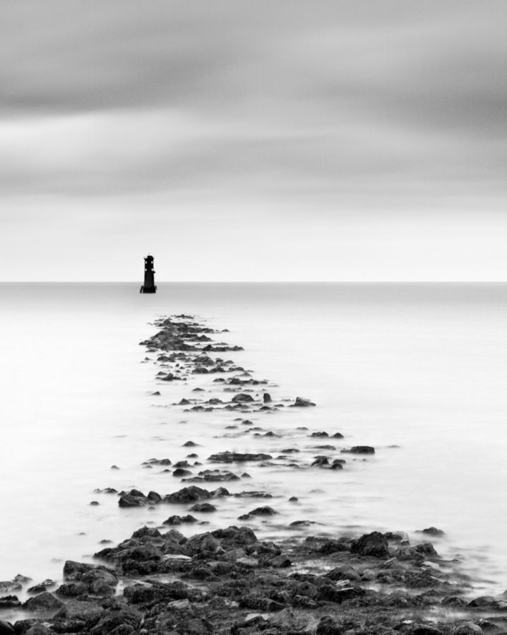 A black and white fine art print featuring an Irish lighthouse. his lighthouse stands at the end of a causeway just off Bull Island in Dublin Bay.
