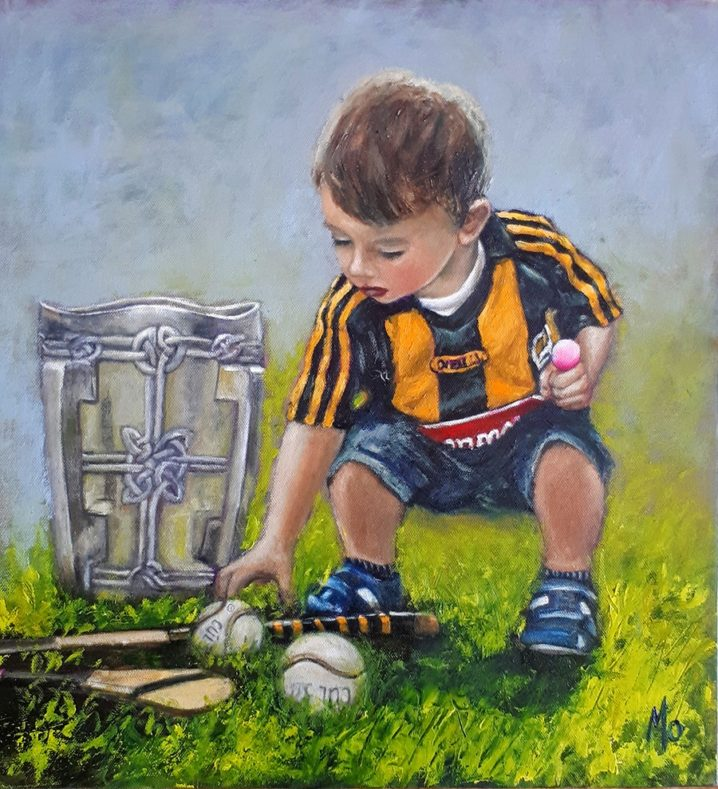 Boy wearing a Kilkenny jersey with a hurley sliotar and the Liam McCarthy Cup.