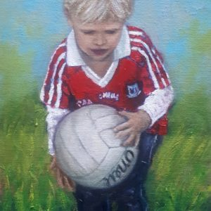 Small boy in a Cork jersey holding a football.
