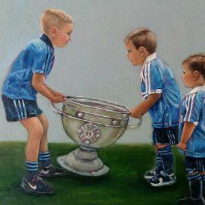 Three boys wearing Dublin jerseys lifting the Sam Maguire.